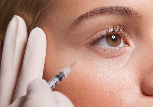 closeup of woman getting an injection in her cheek