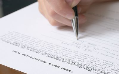 Person writing in their information on an organ donor sheet