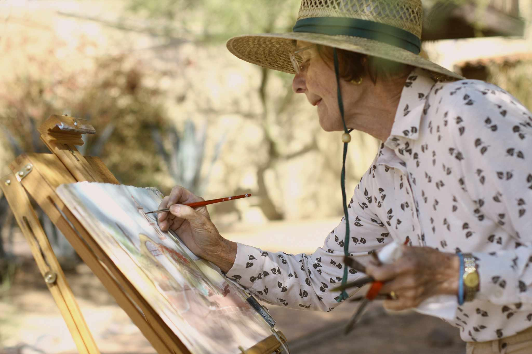 Older woman at an easel painting as part of art therapy for cancer
