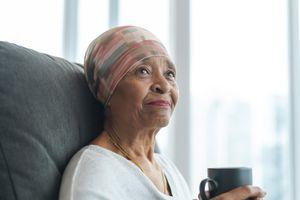 Senior woman wearing headscarf sitting on couch drinking tea