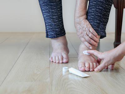 elderly woman putting lotion on feet