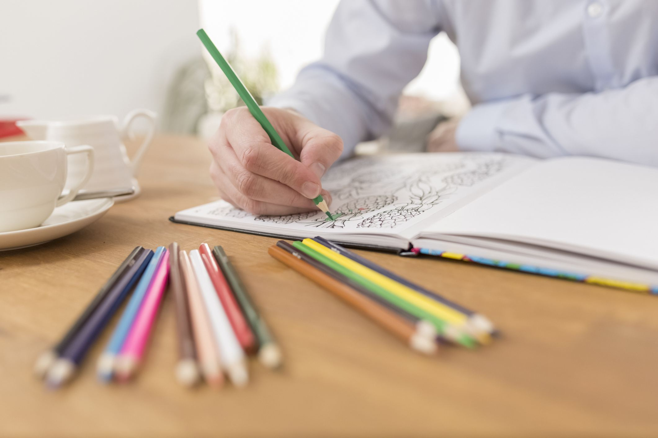 Close up of a man's hand as he colors in an adult coloring book.