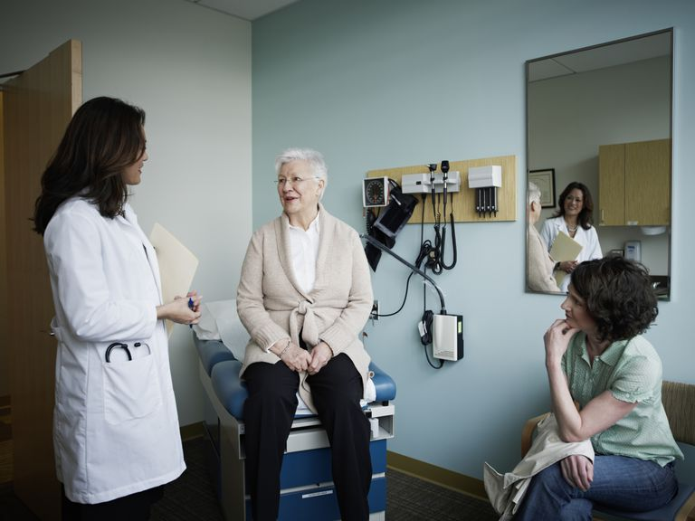 Mature woman and adult daughter talking with a doctor