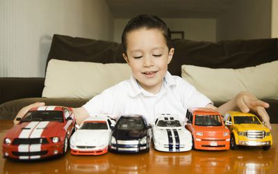 An young child lining up his toy cars