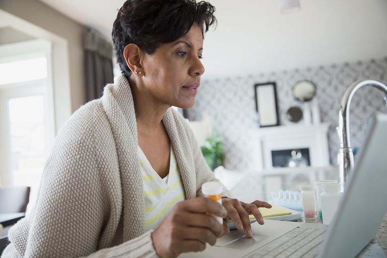 Woman with prescription bottle at laptop.