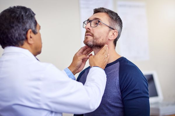 Doctor examining a man's neck
