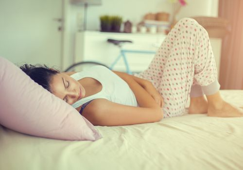 Woman laying on bed holding stomach