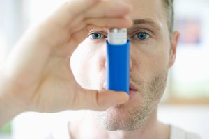 Mid-adult man inhaling asthma inhaler, close-up