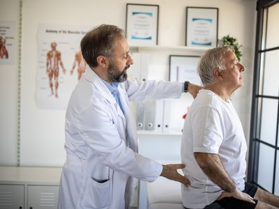 Physical therapist examining senior patient's back injury at doctor's office