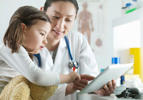 Doctor with girl looking at a tablet