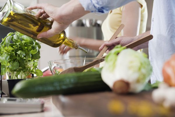 Pouring olive oil on a salad