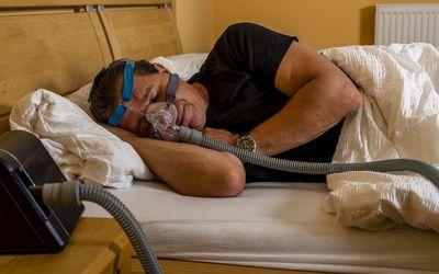 man sleeping with CPAP machine