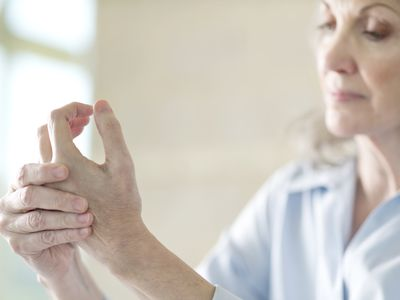 An older woman holding her hand in pain