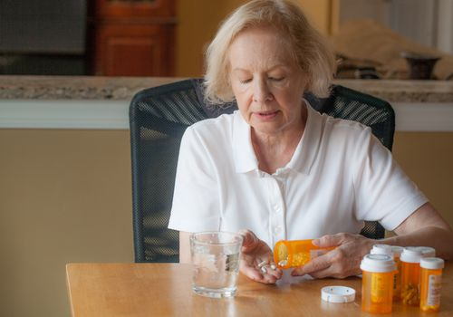 Senior woman taking her daily medicine