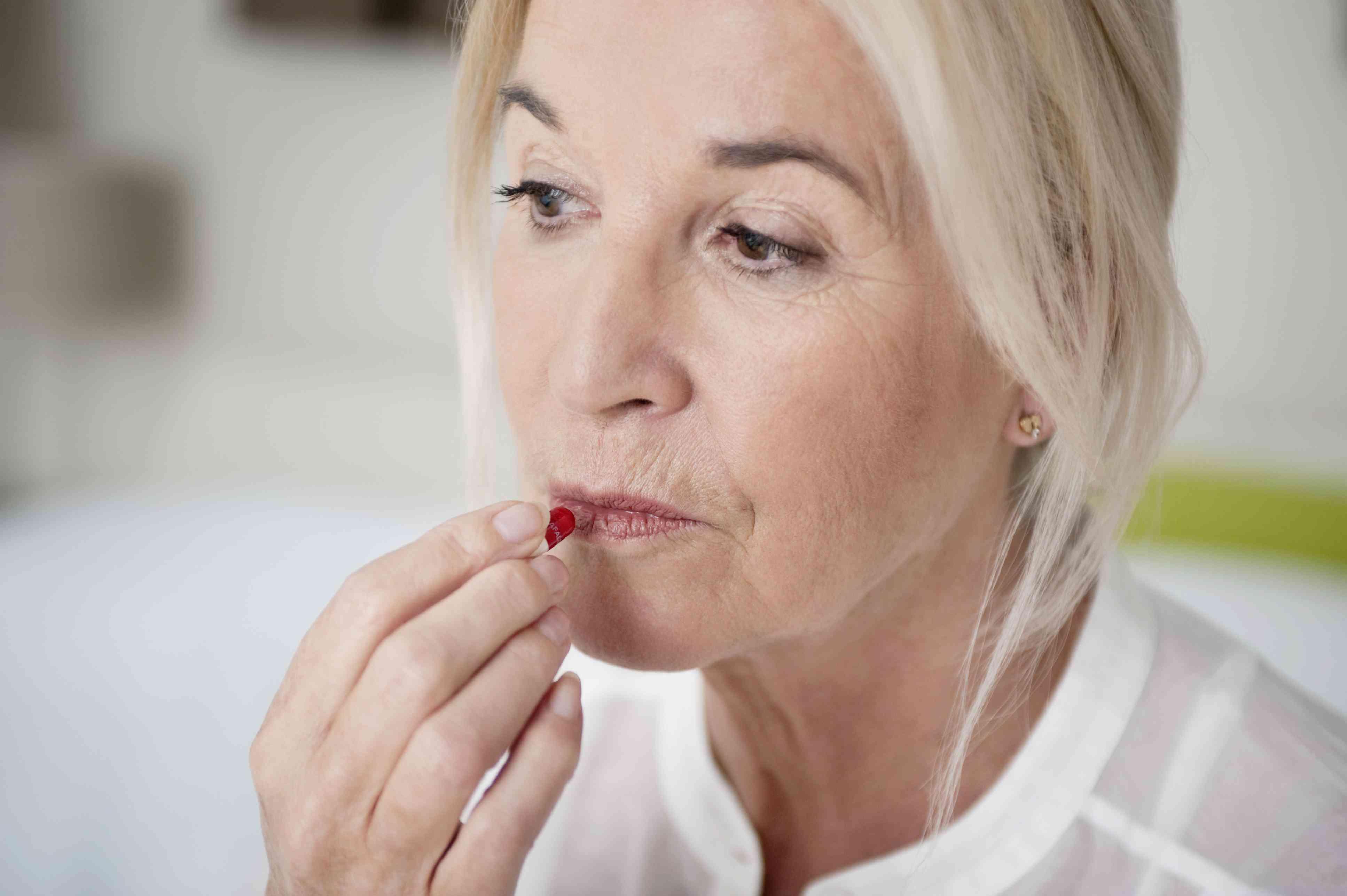Woman about to take a pill