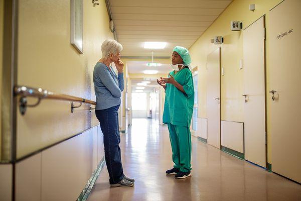 Surgeon talking with senior woman in hospital hallway - stock photo
