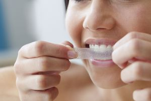 A woman applying a whitening strip to her teeth