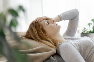 Woman with headache laying back with hand on forehead