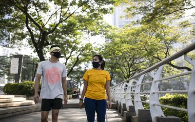 Two people wearing masks walking in the park.