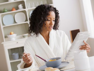 Woman reads while eating
