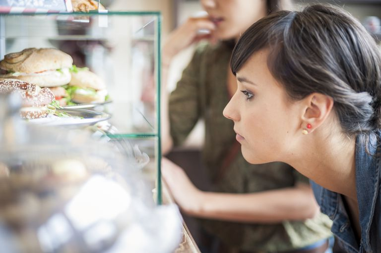 woman staring wistfully at food