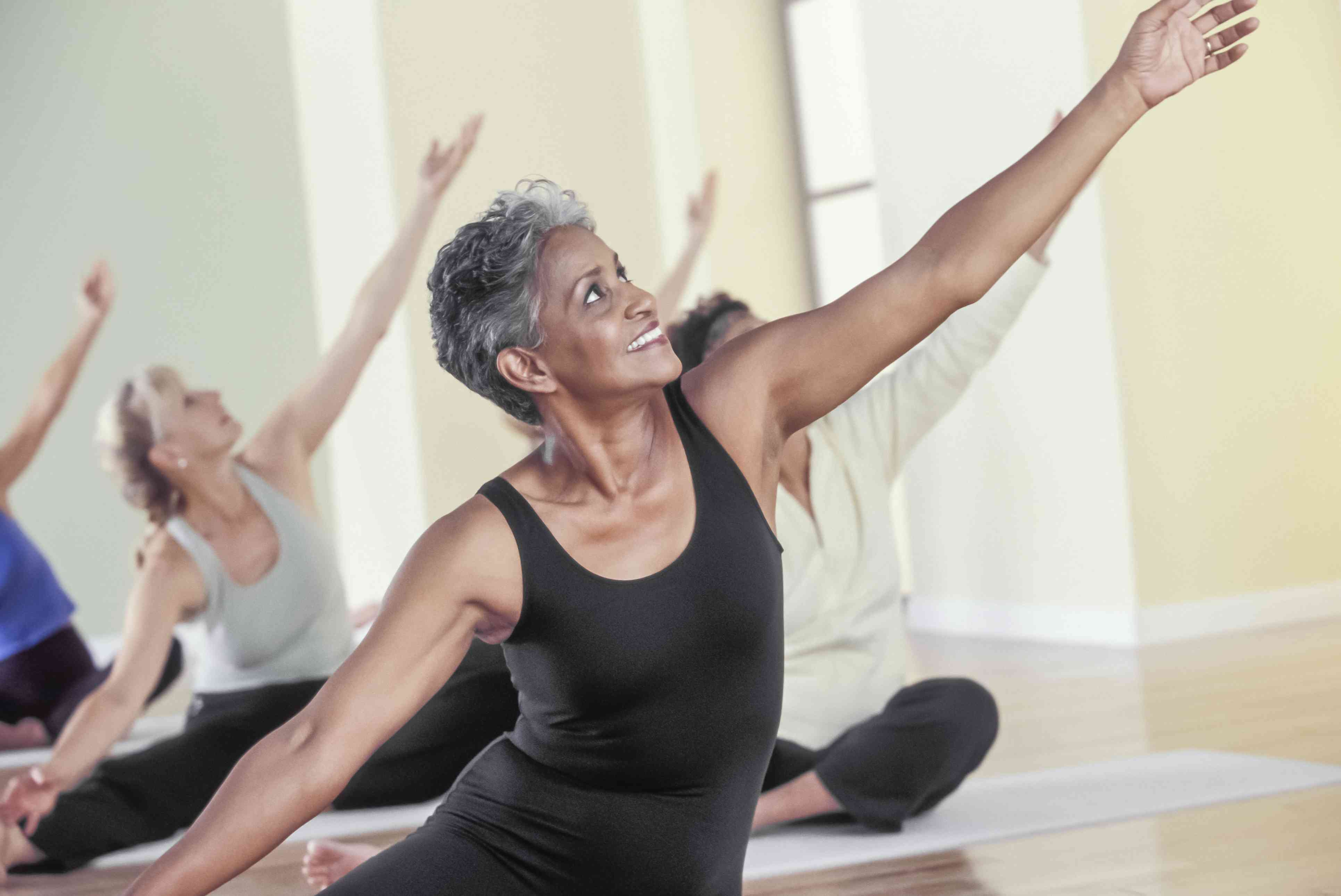 Senior woman stretching in a group exercise class
