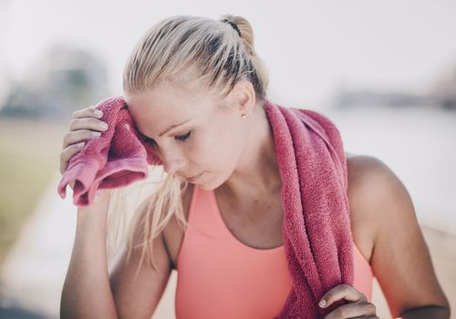 Woman wiping sweat from her forehead with a towel