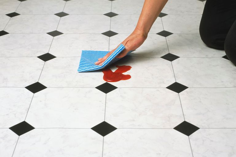 Person wiping a spill off the kitchen floor