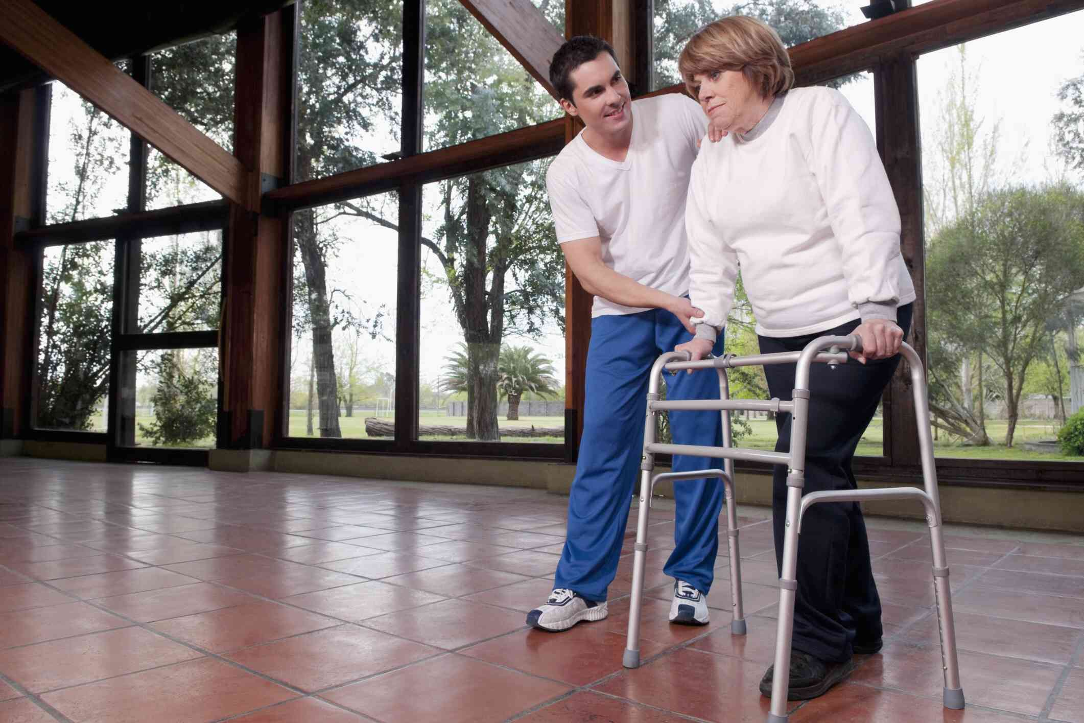 Photo of a woman with a walker working with a physical therapist