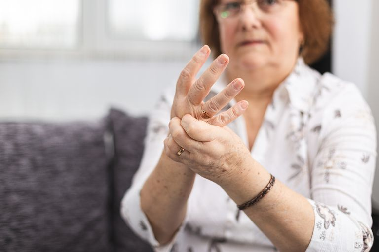 Photo of a woman with arthritis rubbing her sore hand