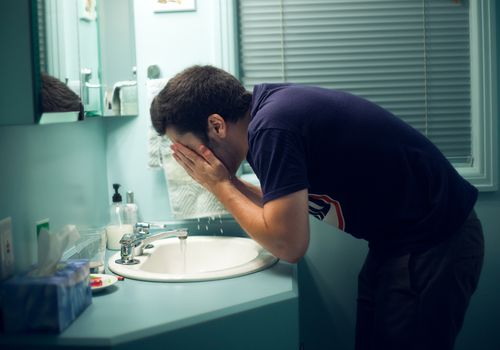 Man washing his face with tap water