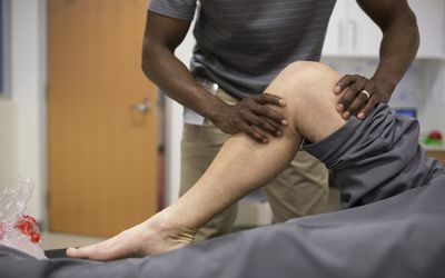 Photo of a man examination a patient's knee.