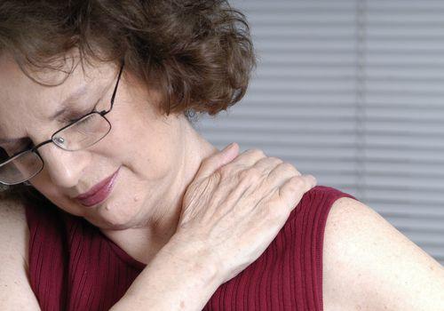 Woman rubbing her aching shoulder