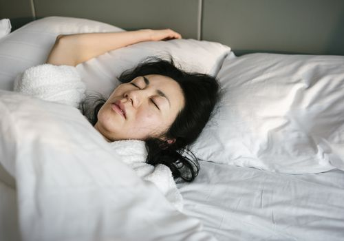 Sick and tired woman sleeping in the bed in early morning