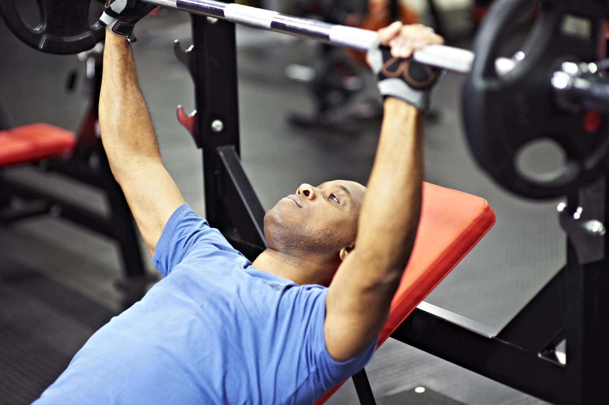 Photo of a man performing a bench press.