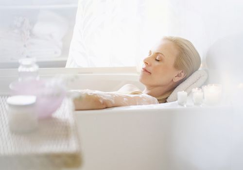 A woman relaxes in the bathtub.