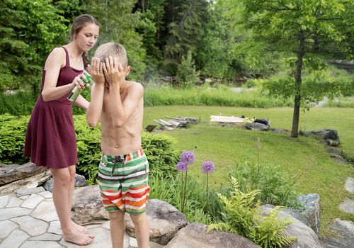 Teenager spraying insect repellant on boy in summer nature.