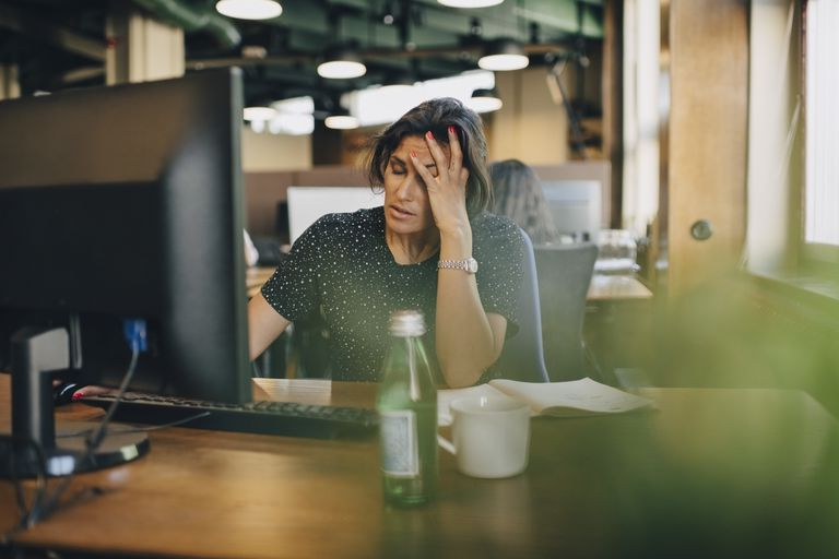 Tired businesswoman with head in hand sitting at computer desk in office - stock photo