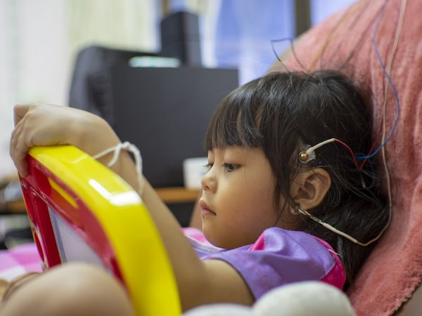 Girl With Electrodes On Head Relaxing On Chair