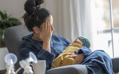 Tired mother holding her newborn child at home after trying to pump