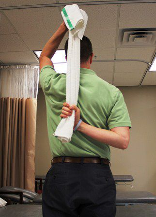 Use a towel to bring the arm up behind the back to stretch the shoulder.