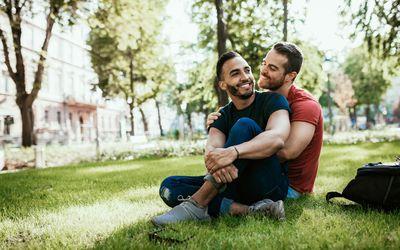 Gay couple - Latino and European millennial men - enjoying in park in summer - stock photo
