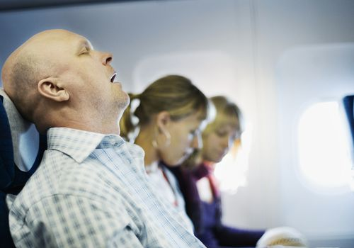 man snoring on airplane