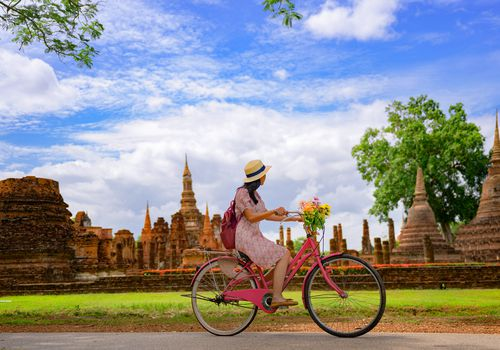 woman riding bike in front of ruins in Thailand