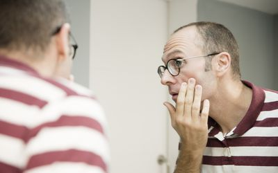Over shoulder view of mature man looking at his face in bathroom mirror