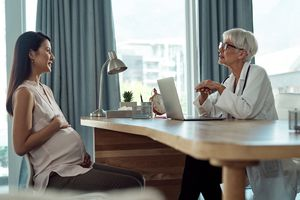 Cropped shot of a mature female doctor using a laptop while having a discussion with her pregnant patient in her office