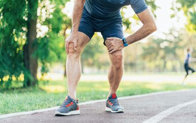 Man on running path stopped holding knee