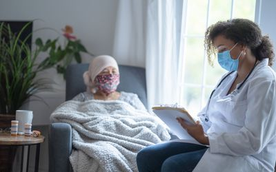 Senior asian female cancer patient wearing mask talking to doctor