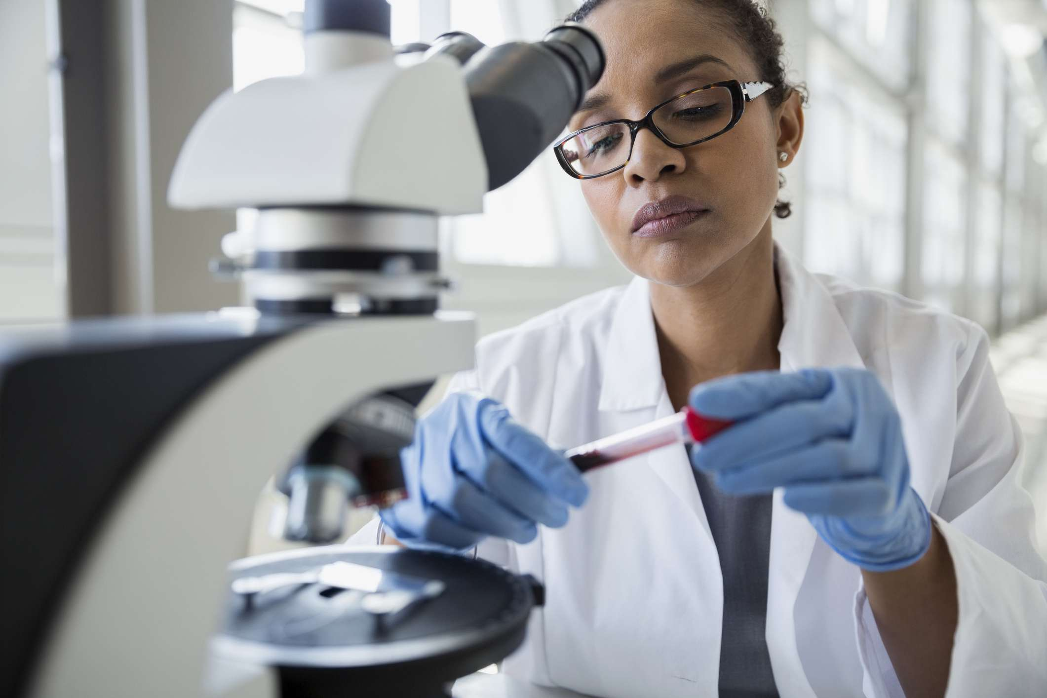 A scientist at a microscope examining a blood sample test tube