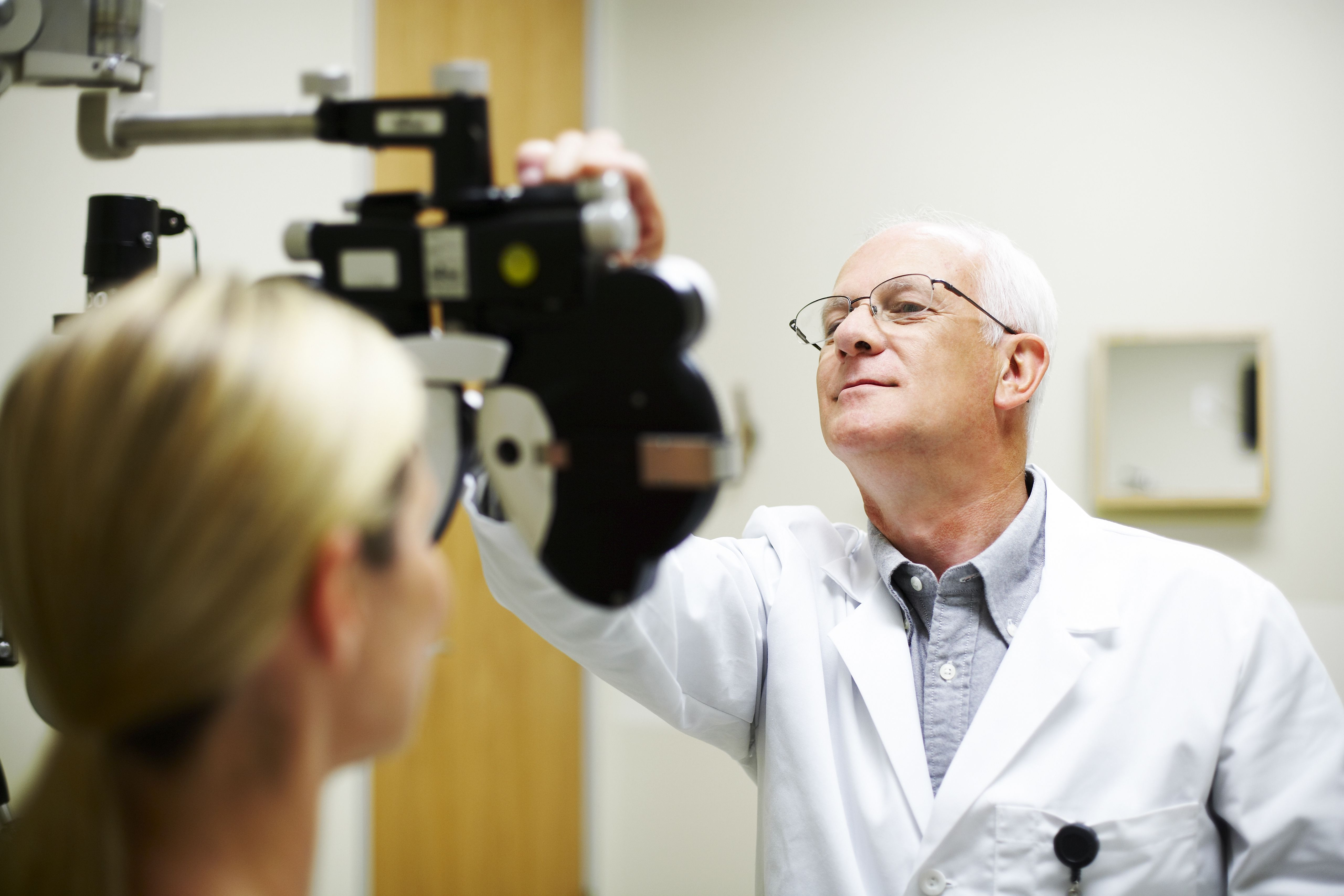 Opthamologist measuring patient's eyesight